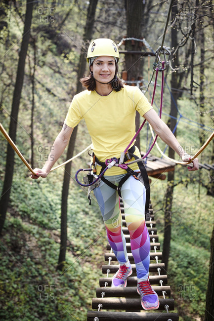 Young woman wearing yellow t-shirt and helmet and rainbow pants in a rope course