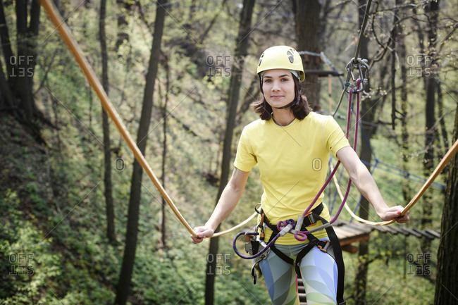 Young woman wearing yellow t-shirt and helmet in a rope course
