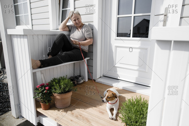 Relaxed senior woman sitting on porch with her dog
