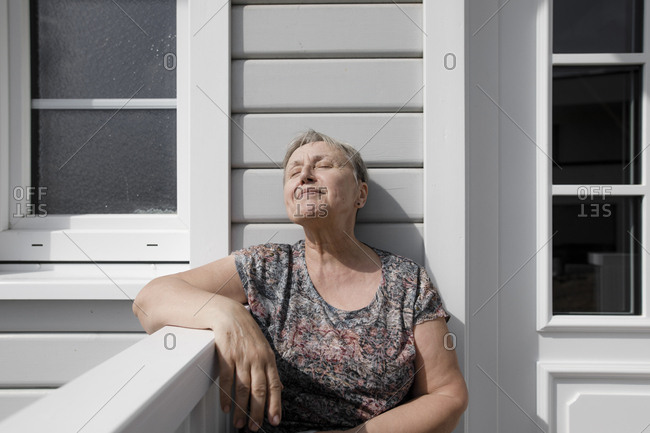 Relaxed senior woman sitting on porch in sunshine