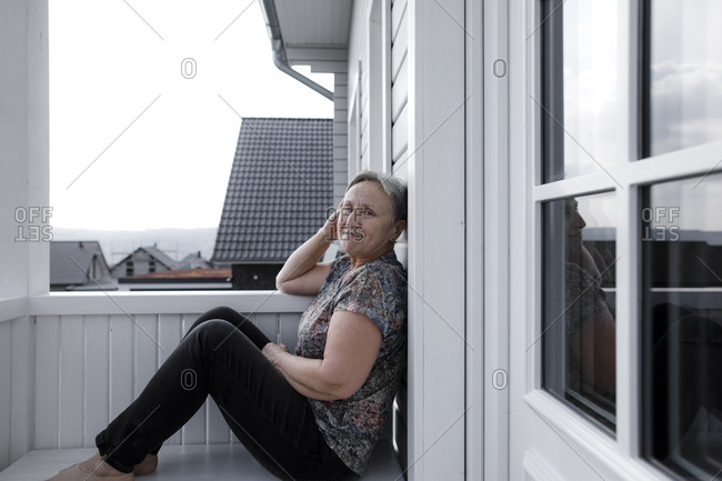 Portrait of smiling relaxed senior woman sitting on porch