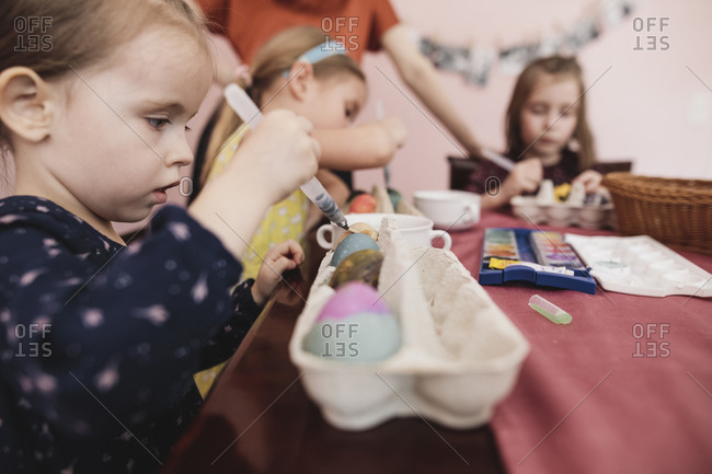 Girls painting Easter eggs on table at home