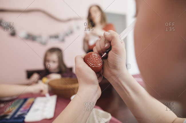 Girl painting Easter egg at home with family in background