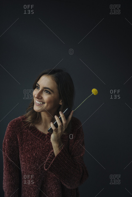 Smiling young woman using flower as antenna for cell phone