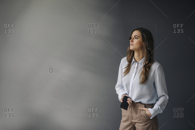 Portrait of serious young businesswoman with cell phone looking sideways