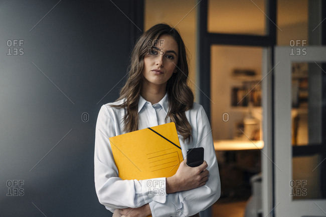 Portrait of serious young businesswoman holding folder and cell phone