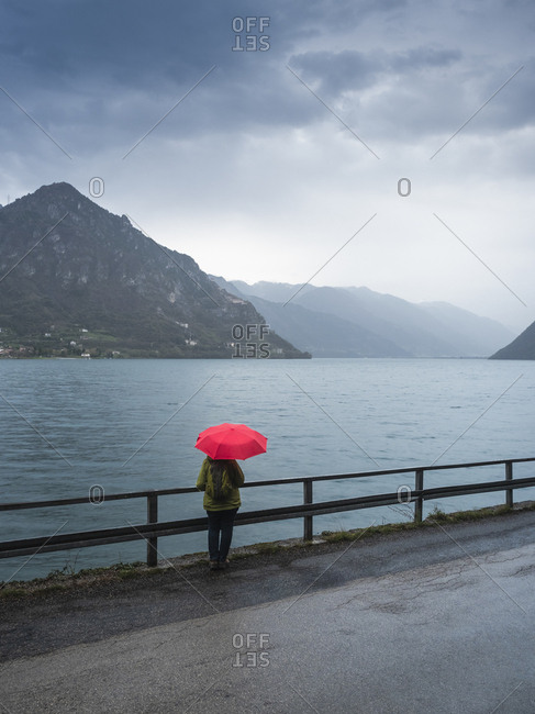 Italy- Lombardy- back view of senior woman with backpack and red umbrella looking at Lake Idro