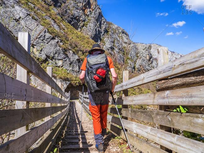 Spain- Asturia- Cantabrian Mountains- senior man on a hiking trip crossing a bridge