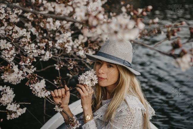 Japan- Tokio- Chidorigafuchi Park- woman in rowing boat smelling at cherry tree blossom