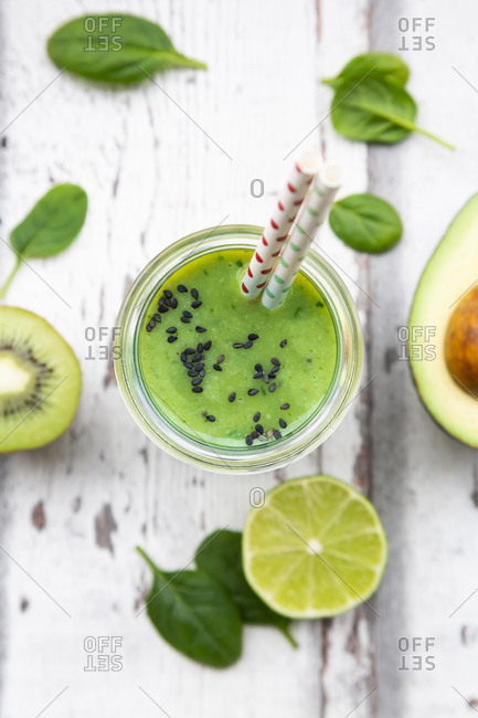 Glass of green smoothie with avocado- spinach- kiwi and lime