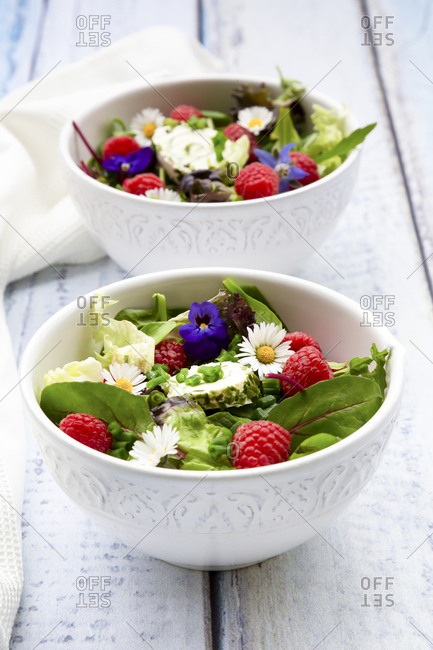 Two bowls of leaf salad with raspberries and cream cheese garnished with edible flowers