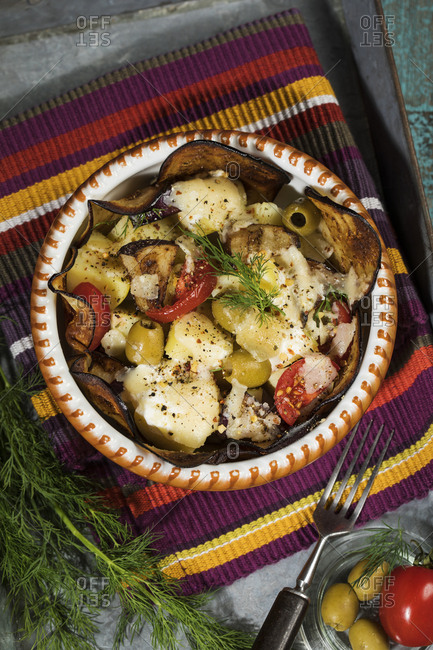Casserole with aubergines- tomatoes- potatoes and green olives garnished with dill