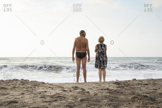 Italy- Sicily- senior couple at the beach looking at the sea