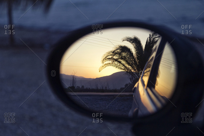 Greece- reflection of palm in wing mirror of a car at sunset