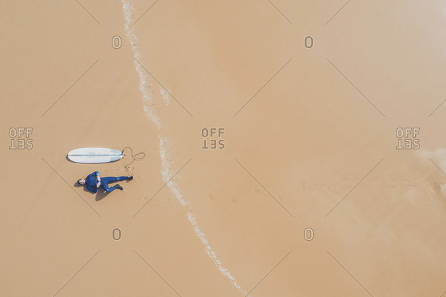Portugal- Algarve- Sagres- Praia da Mareta- aerial view of man lying next to surfboard on the beach