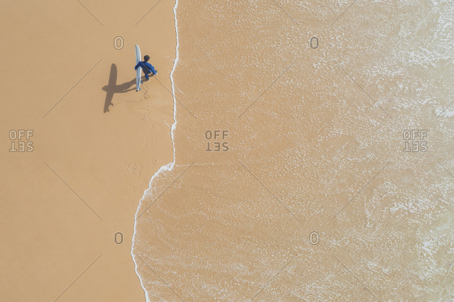Portugal- Algarve- Sagres- Praia da Mareta- aerial view of man carrying surfboard on the beach