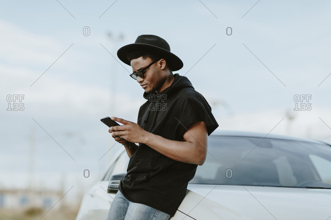 Portrait of a young man sending an email with the phone