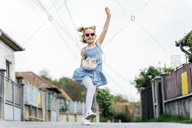 Happy little girl dancing on the street