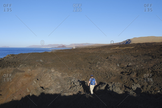 Spain- Canary Islands- Lanzarote- Tinajo- Los Volcanos nature park- women hiking through lava waste