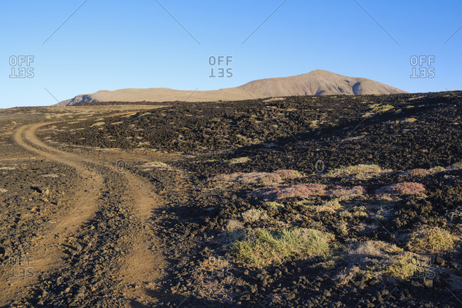 Spain- Canary Islands- Lanzarote- Tinajo- Los Volcanos nature park- traffic lane through lava field