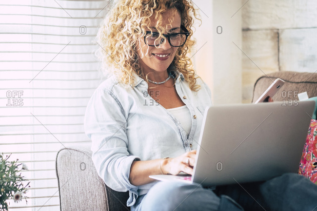 Smiling woman using laptop and cell phone on couch at home
