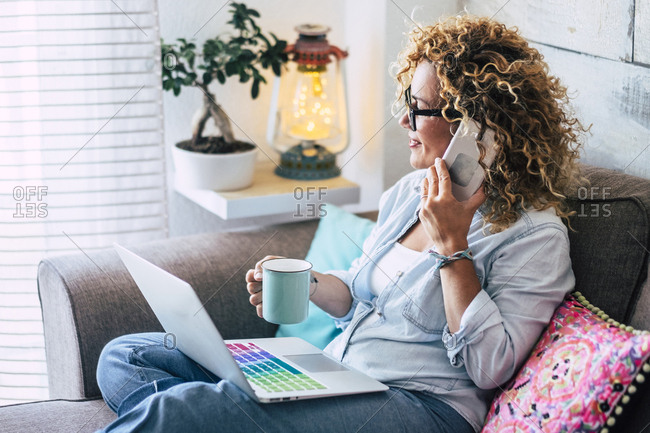 Woman on couch at home with coffee mug- laptop and cell phone