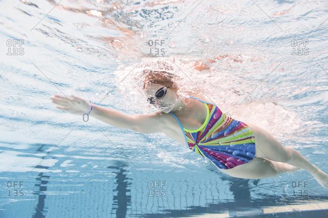 Young woman swimming in swimming pool- crawl- underwater