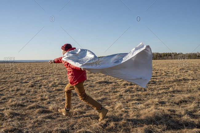 Boy dressed up as superhero running in steppe landscape