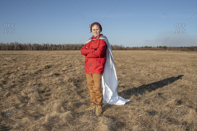 Boy dressed up as superhero posing in steppe landscape