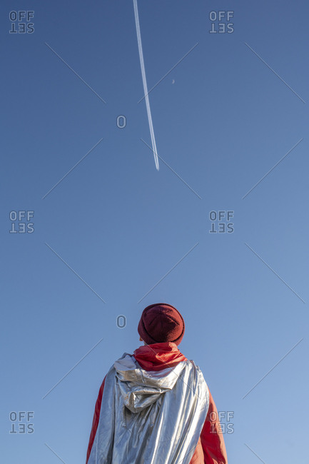 Rear view of boy dressed up as superhero looking at vapor trails in the sky