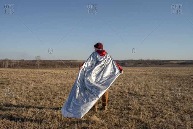 Rear view of boy dressed up as superhero standing in steppe landscape