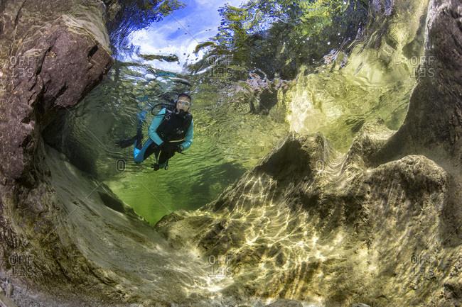 Austria- Salzkammergut- river Weissenbach- female scuba diver in a wild mountain river