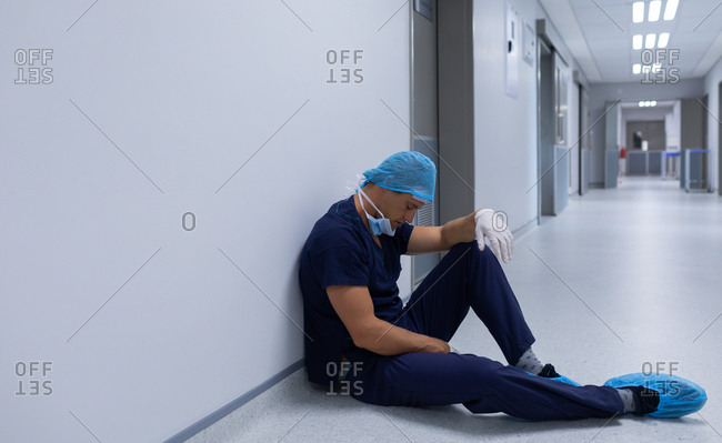 Side view of handsome tensed Caucasian male surgeon with surgical gloves sitting in the corridor at hospital