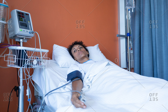 Front view of thoughtful mixed-race female patient lying in bed in the ward at hospital