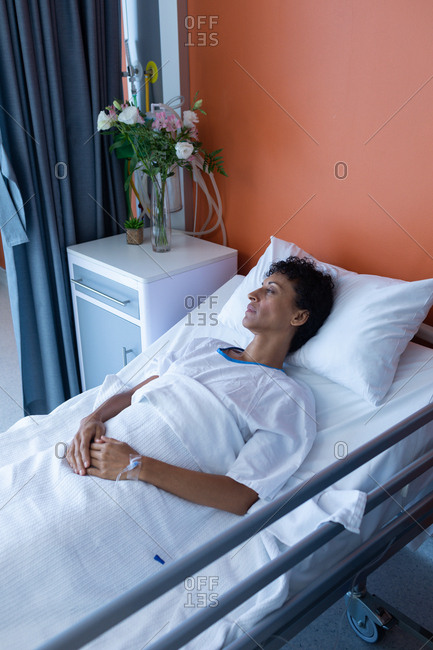High angle view of middle aged mixed-race female patient sleeping in bed with hands on stomach in the ward at hospital