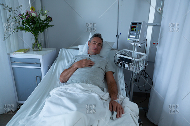 High angle view of mature Caucasian male patient sleeping in bed with right hand on his chest in the ward in hospital