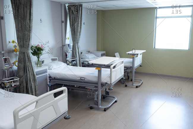 Modern hospital ward with empty beds, medical monitor, green curtains, cupboards, and flowers.