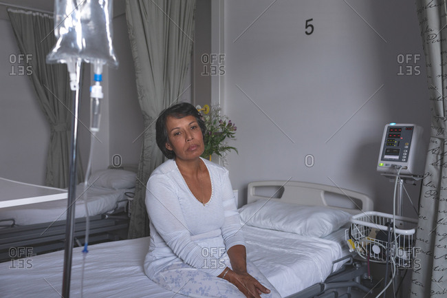 Front view of thoughtful mature mixed-race female patient sitting on bed in the ward at hospital