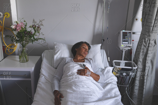 High angle view of mixed-race female patient sleeping in bed with one hand on stomach in the ward at hospital. Flowers are standing on the cupboard next to the bed.