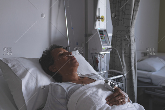 Portrait of mature mixed-race female patient sleeping in bed in the ward at hospital