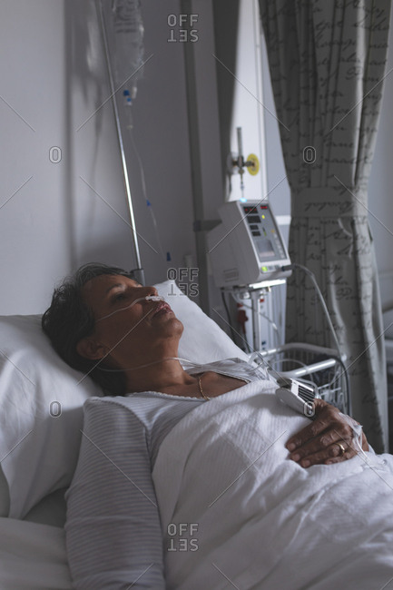 Front view of mature mixed-race female patient sleeping in bed in the ward at hospital