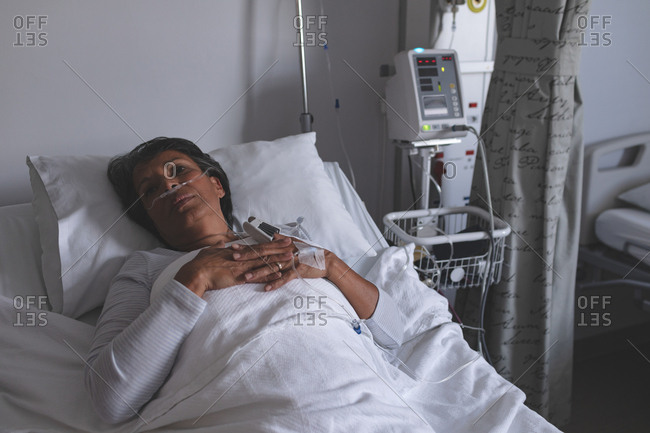 High angle view of thoughtful mixed race female patient relaxing in bed in the ward at hospital. Woman is keeping her hands on chest.