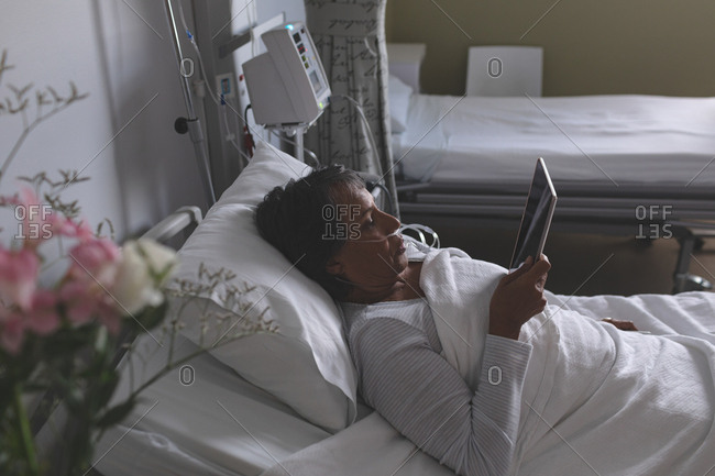 High angle view of beautiful mixed-race female patient using digital tablet in the ward at hospital.