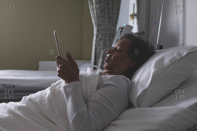 Side view of beautiful mature mixed-race female patient using digital tablet in the ward at hospital.