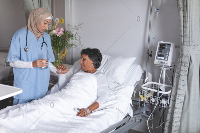 Front view of beautiful mixed-race female doctor in hijab giving medicine to mixed-race female patient in the ward at hospital.