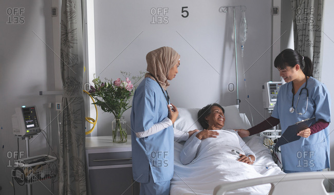 Front view of diverse female doctors interacting with mature mixed-race female patient in the ward at hospital. Female patient is looking relieved.