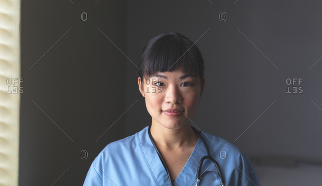 Portrait of happy beautiful Asian female doctor standing with stethoscope around neck in hospital