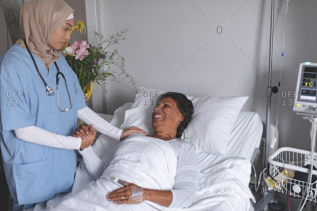 Front view of mixed race female doctor in hijab consoling mature mixed race female patient in the ward at hospital.