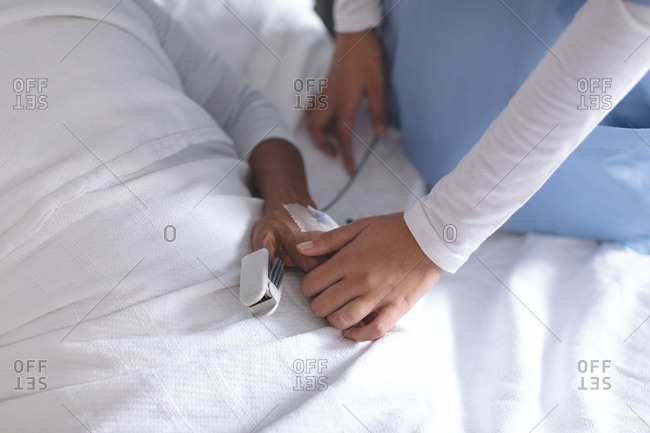 Mid section of female doctor consoling female patient in the ward at hospital