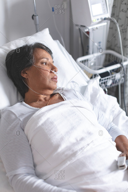 High angle view of thoughtful mixed-race female patient relaxing in bed in the ward at hospital
